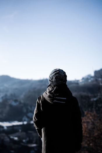 Rear view of person against clear sky during winter