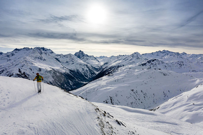 Rear view of person on snowcapped mountain against sky