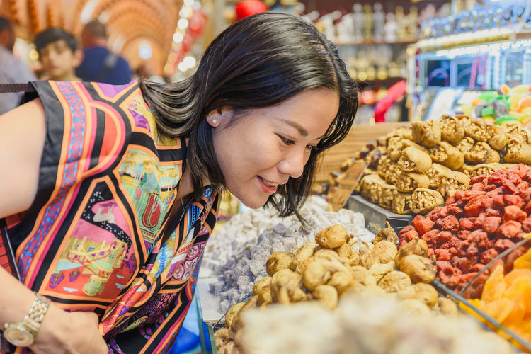 Close-up of smiling woman looking at dried food in market