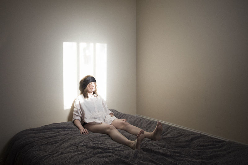 Woman sitting on bed against wall at home