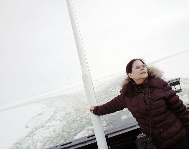 Aboard Adult Adults Only Beauty In Nature Cold Temperature Day Jacket Leisure Activity Motion Nature One Person One Young Woman Only Outdoors People Real People Sail Sea Sky Snow Vacations Warm Clothing Water Winter Young Adult Young Women