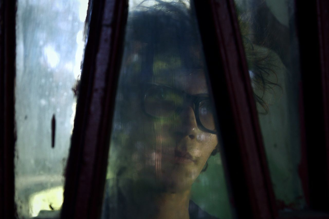 CLOSE-UP OF REFLECTION OF MAN IN GLASS WINDOW