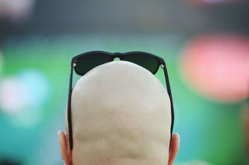 Rear View Of Man With Shaved Head Wearing Sunglasses