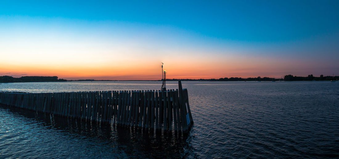 Beauty In Nature Blue Calm Clear Sky Distant Majestic Nature No People Non-urban Scene Ocean Orange Color Outdoors Pole Rippled Scenics Sea Seascape Sky Sunset Tranquil Scene Tranquility Water Waterfront Wooden Post