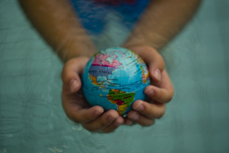 Above close up looking down on hands holding the world over water Atlantic Ocean Hand Holding Hands Map Plant Power USA America Canada Cat Citizen Of The World Citizenship Continent Ecology Energy Ocean Planet Protection Refugees South America Sustainability Sustainable Sustainable Resources Water World