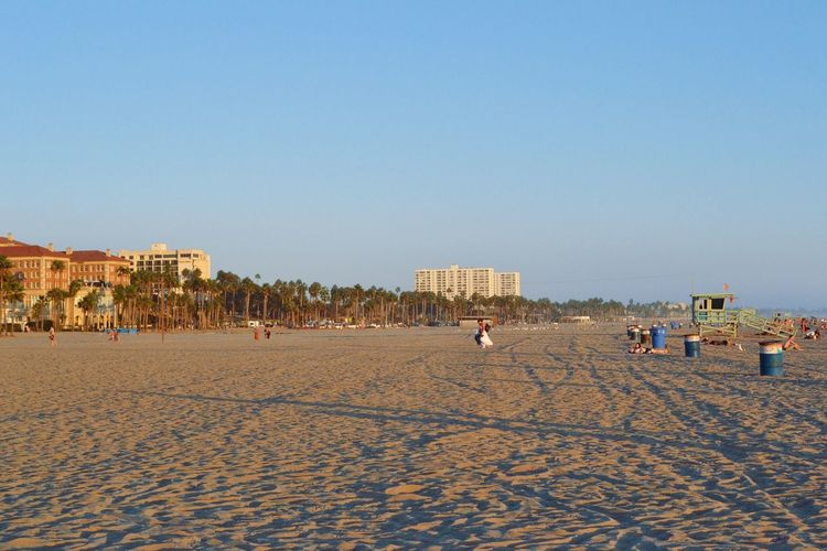 Scenic View Of Beach By City Against Clear Sky