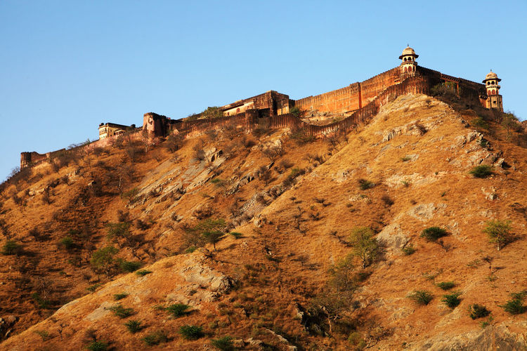 Low Angle View Of Amer Fort On Mountain Against Clear Sky