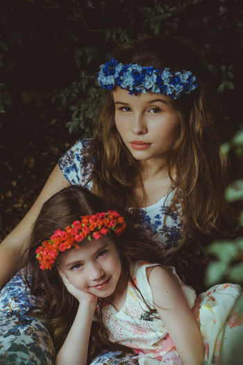Portrait Of Girl With Sister Wearing Flowers On Hair