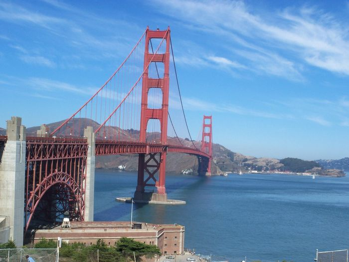 Low Angle View Of Red Golden Gate Bridge Over River Against Sky On Sunny Day