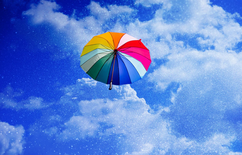 Low angle view of umbrella flying against sky