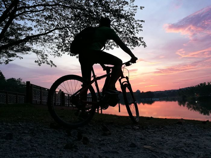 Sunset Reflection Silhouette Tree Water Bicycle Lake Sky Landscape People Outdoors Nature Only Men Adult One Man Only One Person Day Visual Creativity