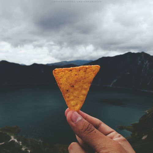 Person holding chip against lake sky