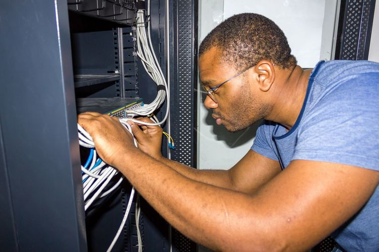 Side View Of Man Working With Wires