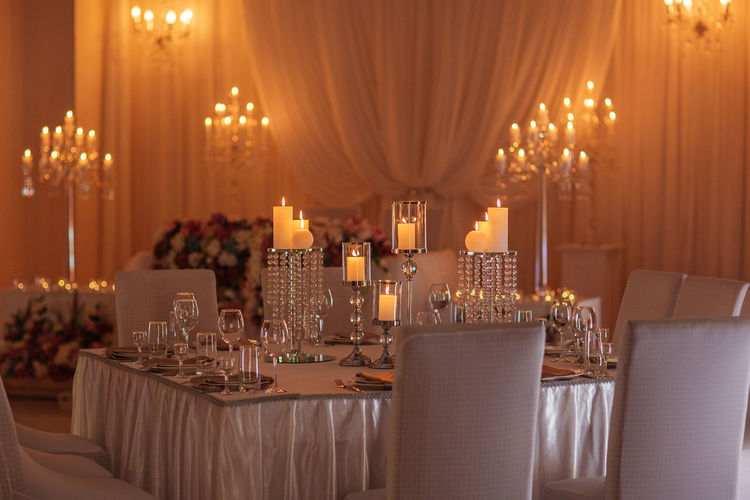 Panoramic view of wine glass on table in illuminated room