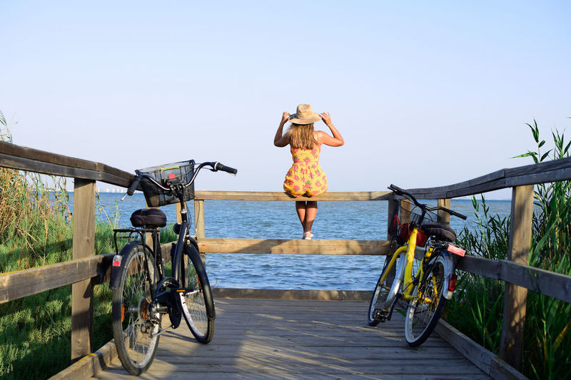 Rear view of woman on bicycle by sea against clear sky