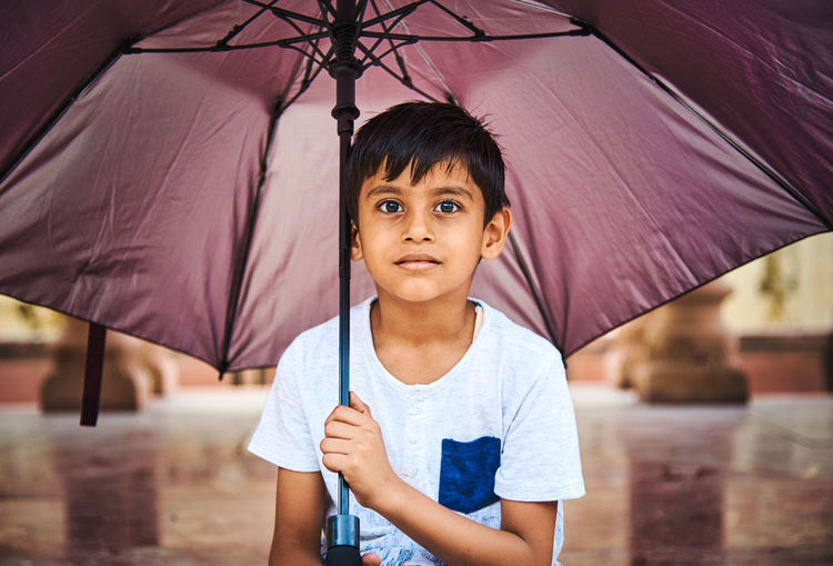 Portrait of cute boy holding umbrella standing outdoors