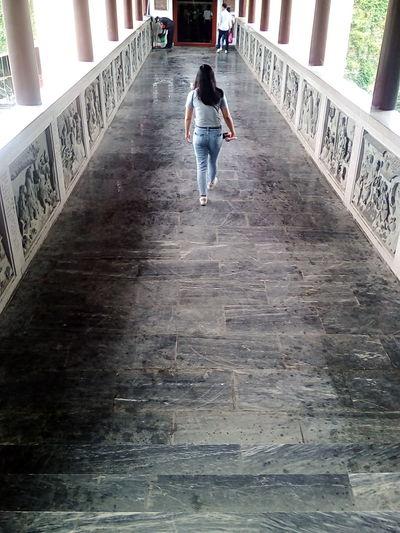 Full length rear view of woman walking on elevated walkway