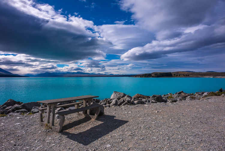 Empty bench and table by lake pukaki against cloudy sky