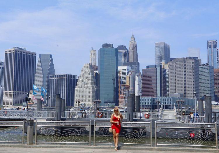 Full length of woman on footbridge in city