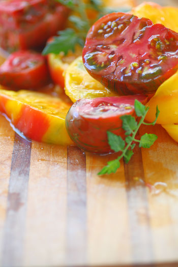 Fresh heirloom tomatoes on cutting board Food Healthy Eating Cutting Board Wood - Material Raw Food No People Indoors  Red Heirloom Tomatoes Fresh Produce Copy Space Room For Text Juicy Delicious Food Preparation Wet Leaves Vertical Food Ingredient Nutritious Colorful Summer Yellow Natural Light