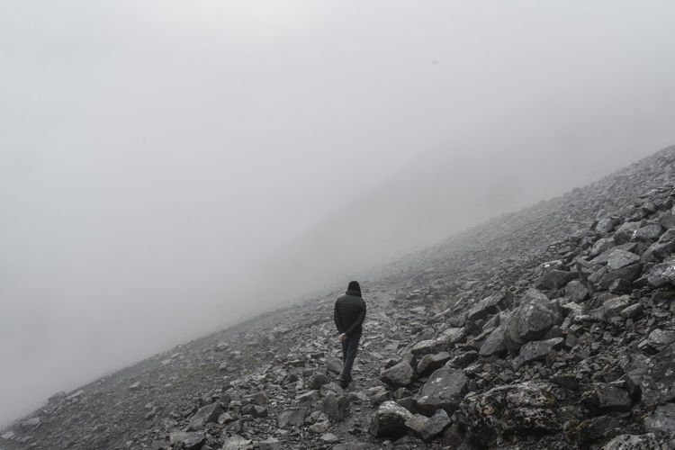 Rear view of man walking on mountain during foggy weather