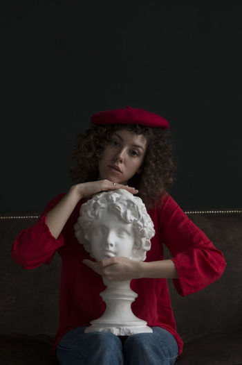 Portrait of woman holding bust