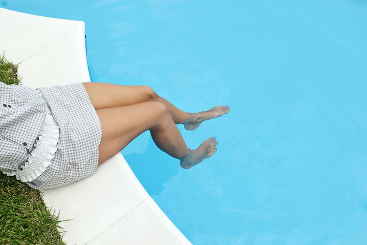 Low section of sensuous woman sitting at poolside