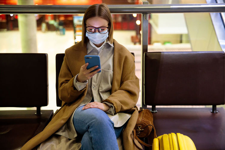 Woman using smart phone while sitting in waiting room