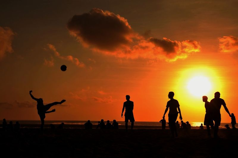 Silhouette people playing with ball at beach against sky during sunset