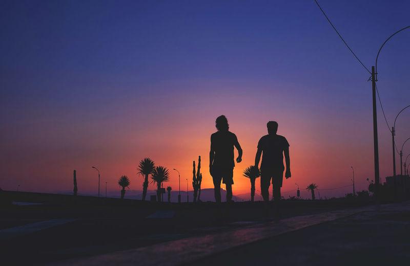 Silhouette people on street against orange sky
