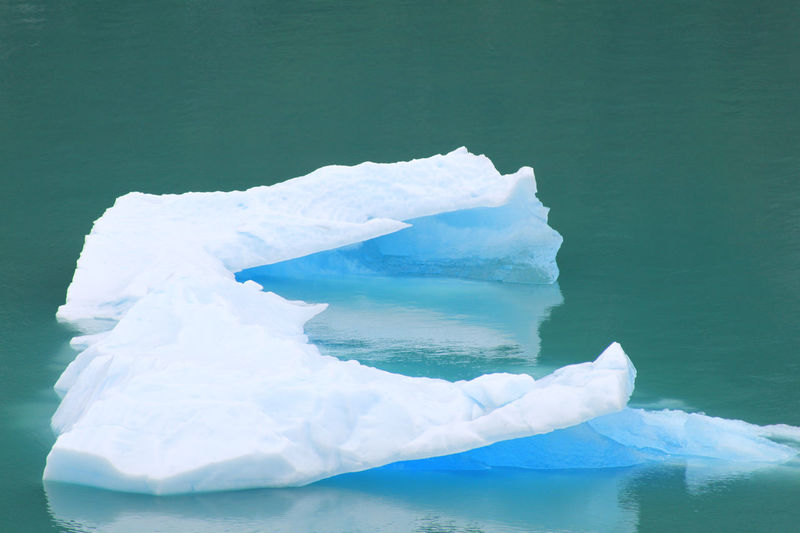 Close-up of snow-covered piece of ice melting while floating on the surface of a mountainous lake