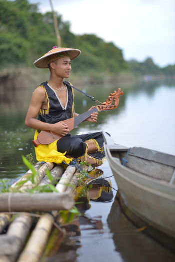 Full length of man playing guitar sitting on boat at lake