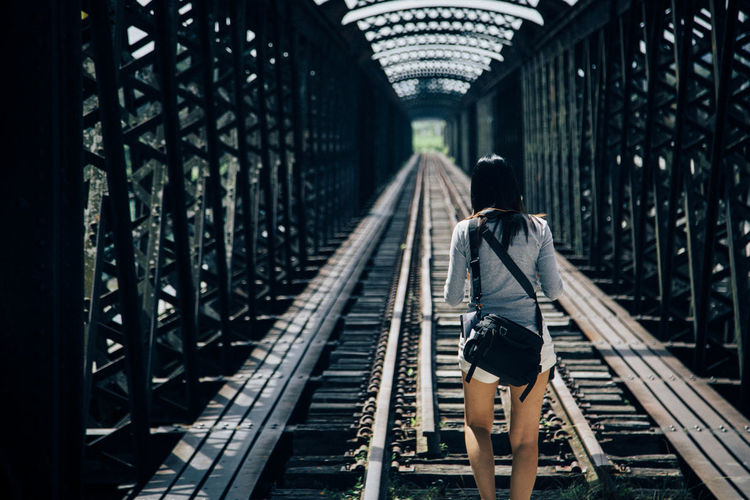 Rear view of woman walking on railway bridge