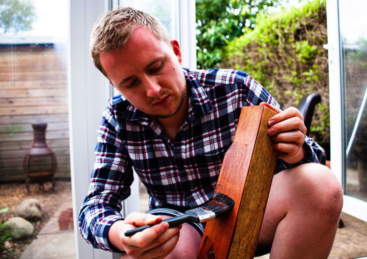 Young man painting wooden plank while crouching in yard