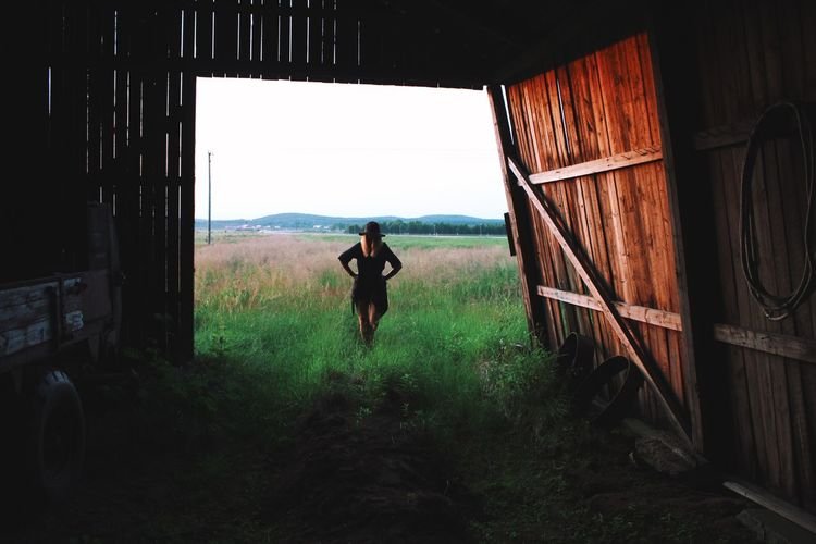 Rear View Of Woman With Hand On Hip Standing Outside Barn