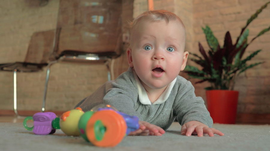 Portrait of cute baby boy with toy on floor