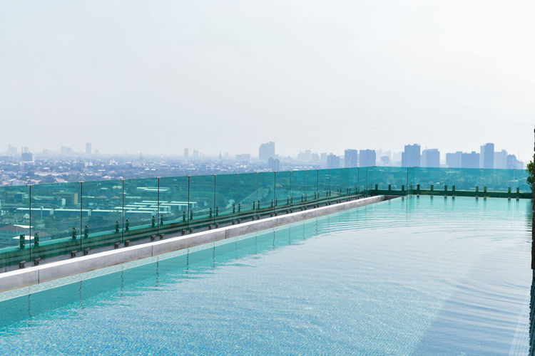 Swimming pool by city against sky