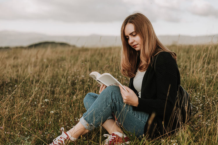 Woman reading a book outdoors on top of the mountain