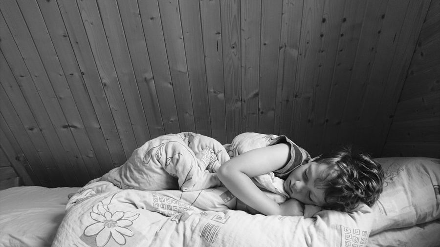 Boy sleeping on bed against wall at home