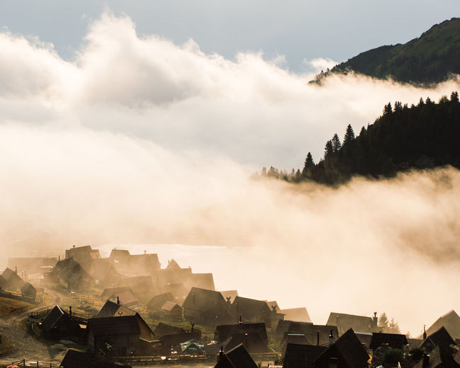 Panoramic view of buildings in mountains against sky