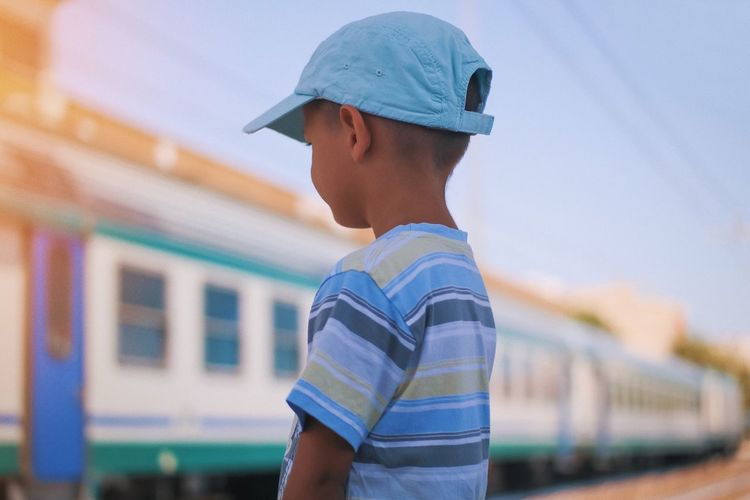 Boy looking at train against sky