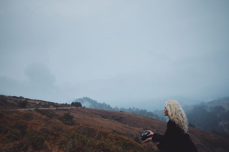 Woman with camera on landscape against sky
