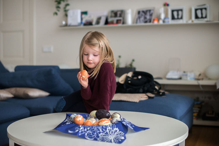 Girl Looking At Easter Egg While Sitting On Table At Home