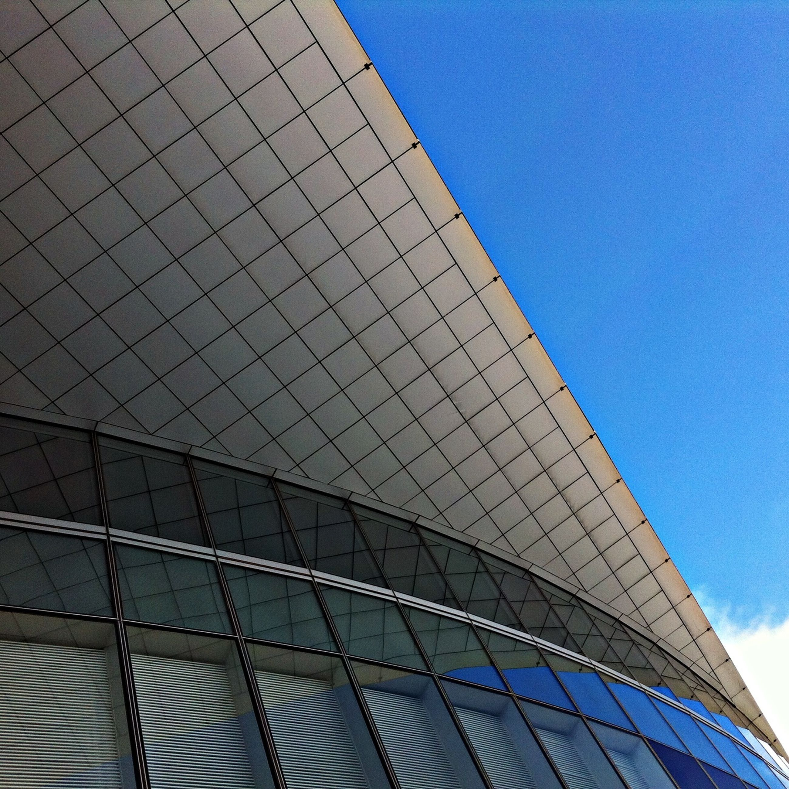 architecture, low angle view, built structure, building exterior, modern, blue, sky, office building, city, glass - material, building, reflection, pattern, tall - high, skyscraper, day, tower, outdoors, no people, architectural feature