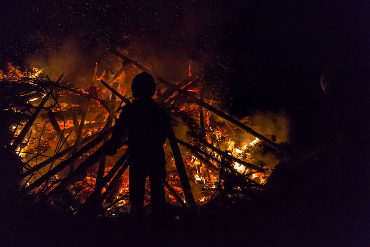 Rear view of silhouette person standing by burning woods at night