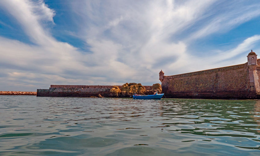 Moored boat on sea against sky