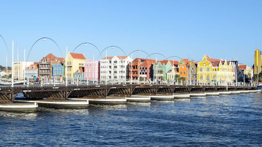 Queen emma pontoon bridge over sea by cityscape against sky