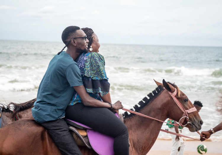 Animal Wildlife Beach Casual Clothing Domestic Domestic Animals Emotion Horizon Over Water Horse Land Leisure Activity Lifestyles Men Real People Riding Sea Togetherness Two People Water Women Young Adult