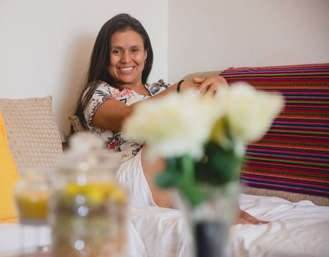Portrait of smiling woman on bed at home