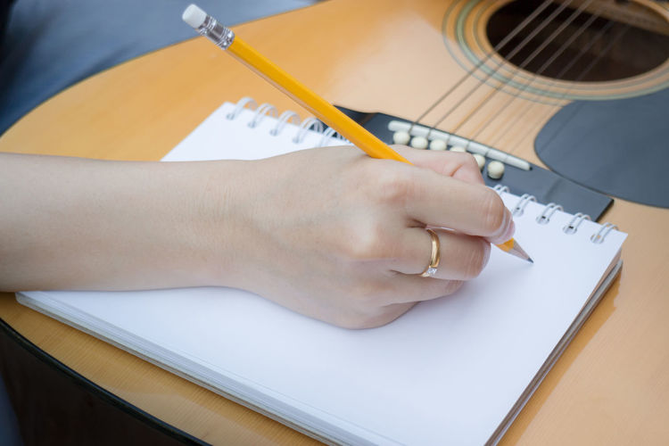 High Angle View Of Men Writing On Diary While Playing Guitar